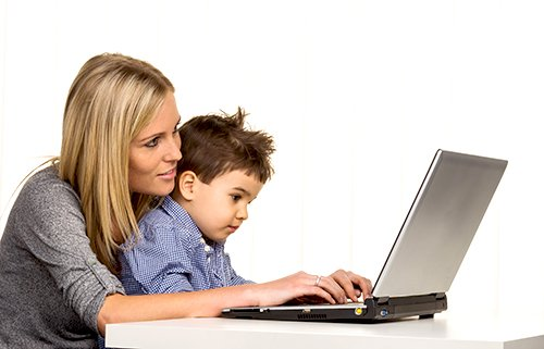 Woman helping child type on laptop computer
