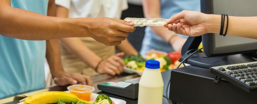 student handing cashier 10-dollar bill in lunch line.