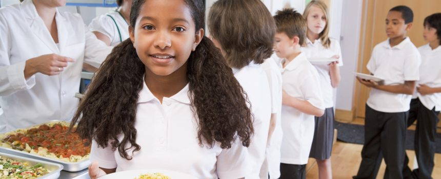 Schoolgirl holding plate of lunch standing at end of queue in school cafeteria