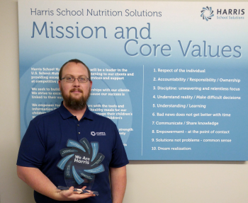 Adam Hansen holding award in front of Core Values poster.