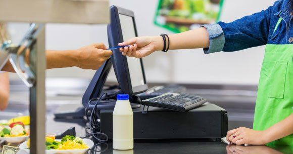 Hands exchanging credit card infront of lunchline pos system.