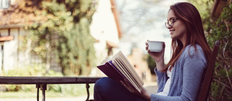 Woman sitting, drinking tea, reading a book.