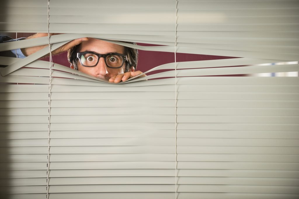 Worried man peeking through blinds at office.