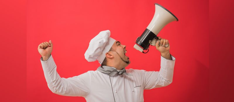 Chef using megaphone in front of red background.